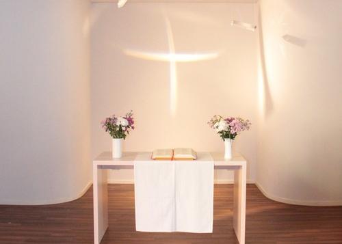 Die Lichtinstallation des Künstlers Dieter Detzner lässt das Kreuz in der Kapelle strahlen.