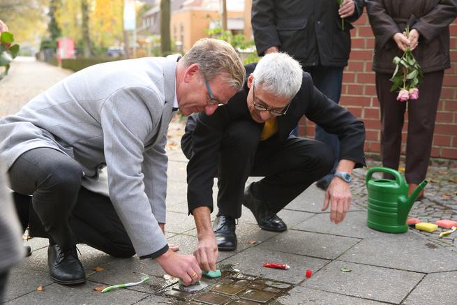 Geschäftsführer Dr. med. Matthias Albrecht (links) und Pfarrer Wolfgang Weiß (rechts) reinigen die Stolpersteine auf dem Gehweg vor dem Evangelischen Krankenhaus Hubertus.