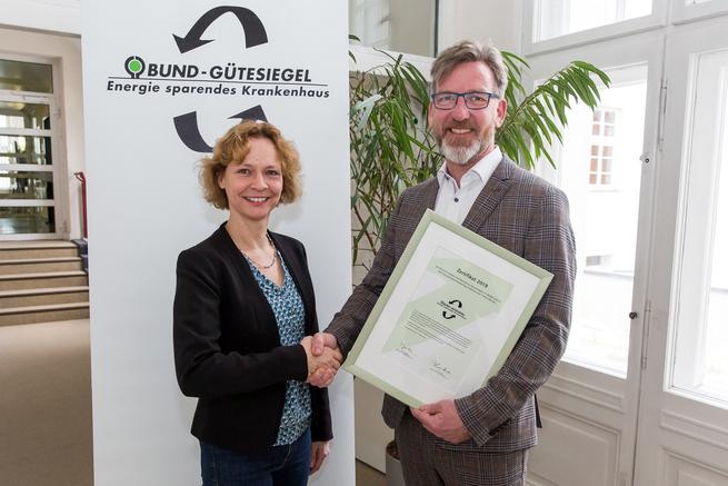 Annegret Dickhoff (BUND, Projektleiterin) überreicht Dr. med. Matthias Albrecht (Geschäftsführer, Evangelisches Krankenhaus Hubertus) das BUND-Siegel 2019