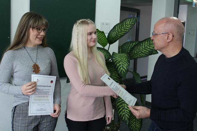 Mathias Held, Leiter der Krankenpflegeschule am Paul Gerhardt Stift, überreicht Anna-Luisa Pötzsch und Julia Lindemann die Nominierungsurkunde für den Vorentscheid der Deutschen Meisterschaft der Pflege.