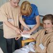 Schon einmal üben für später: Die Pflegekräfte des Evangelischen Krankenhaus Hubertus zeigen, wie man einen Gips anlegt.