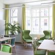 Das gemütliche Wohnzimmer auf der Palliativstation mit Zugang zum barrierefreien Balkon bietet Platz für gemeinsame Aktivitäten, Essen, Besuche.